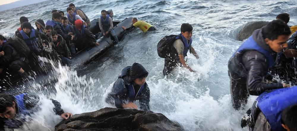 Groupe de réfugiés abordant dans les rochers
